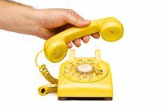 het-opheffen-van-de-hand-handstuk-van-gele-telefoon-23415059